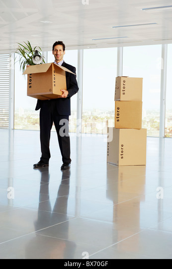 Happy business man holding cardboard box with his belongings in empty office space - Stock Image