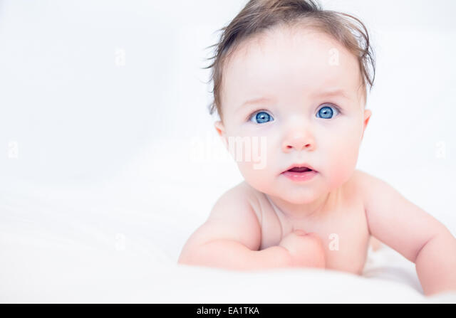 Lovely baby with blue eyes in bed - Stock Image