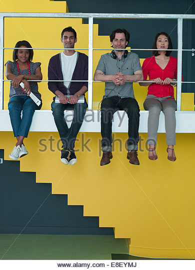 Men and women sitting in a row on ledge - Stock Image
