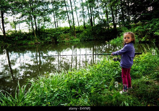 Girl fishing at a lake, Poland - Stock Image