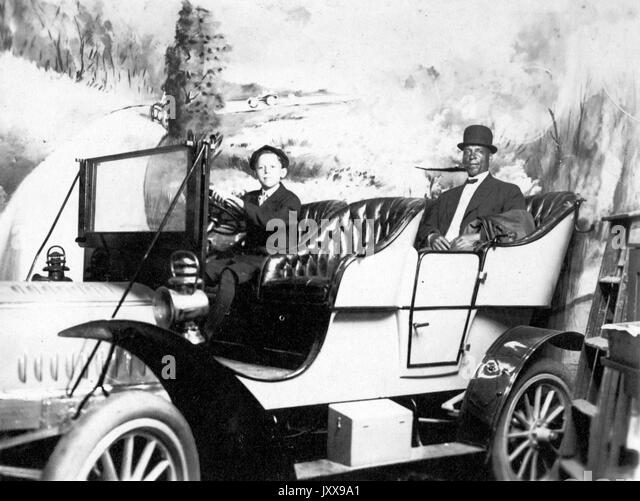 Full length portrait of two men in a car, a young Caucasian boy at the wheel, an African American man in the backseat, - Stock Image