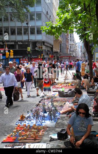 Buenos Aires Argentina downtown Avenida Peru crowded sidewalk busy pedestrian street vendor hawker Hispanic man - Stock Image