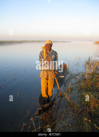One eyed fisherman in dugout canoe on banks of Luapula tributary of Congo River Democratic Republic of Congo - Stock-Bilder