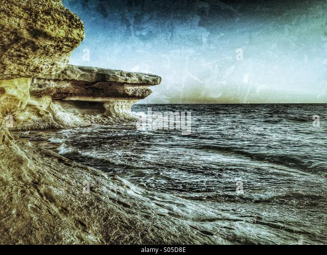 North shore coast showing limestone erosion by wind and waves - Stock Image
