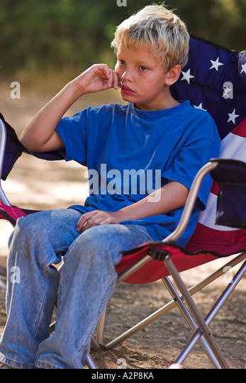 A young boy sits in a chair while camping in the outdoors. - Stock Image