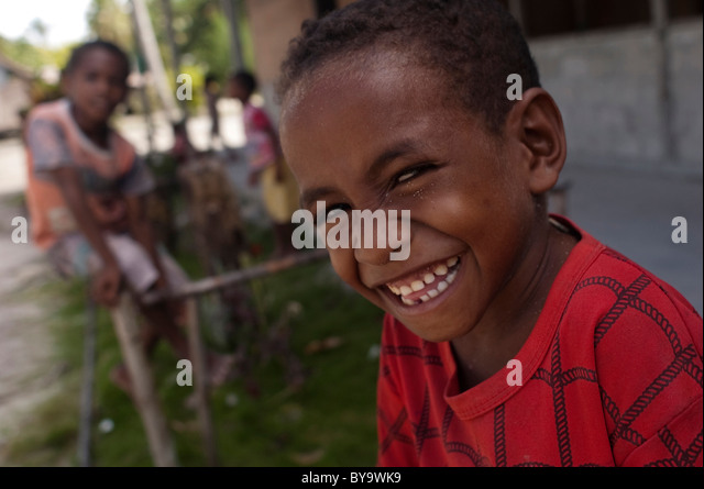 childs sit in front of their abandon school at sauwandarek village, west papua, indonesia - Stock Image