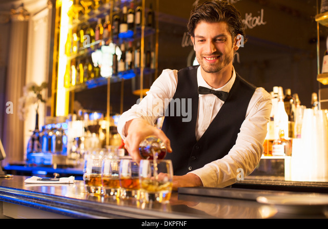 Well dressed bartender pouring bourbon at luxury bar - Stock Image