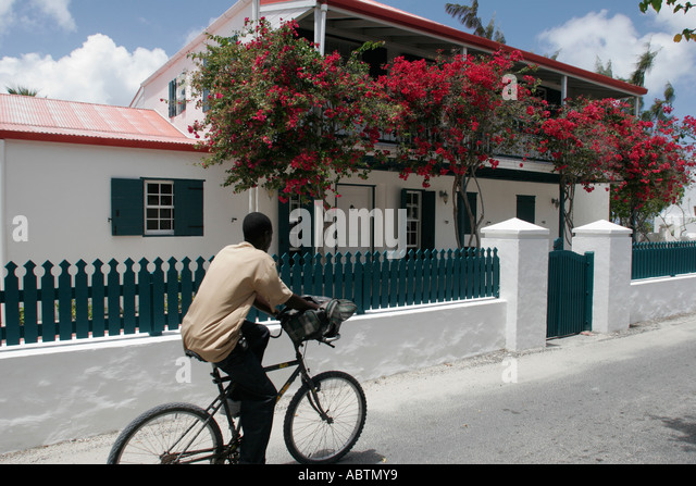 Grand Turk Cockburn Town Duke Street Black man bicycle house wall fence flowering trees - Stock Image