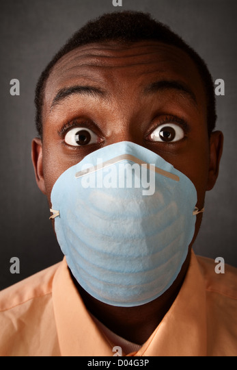 Wide-eyed Black man wearing a surgical mask - Stock Image