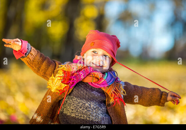 Happy little girl playing in the autumn park - Stock Image
