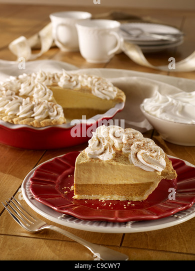 A whole pumpkin cream pie with a slice topped with whip cream - Stock Image