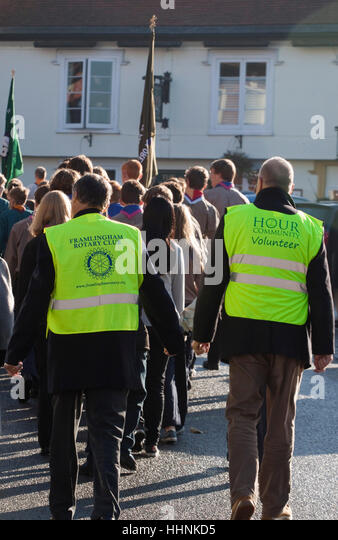 Two male volunteers in yellow hiviz follow a parade - Stock Image