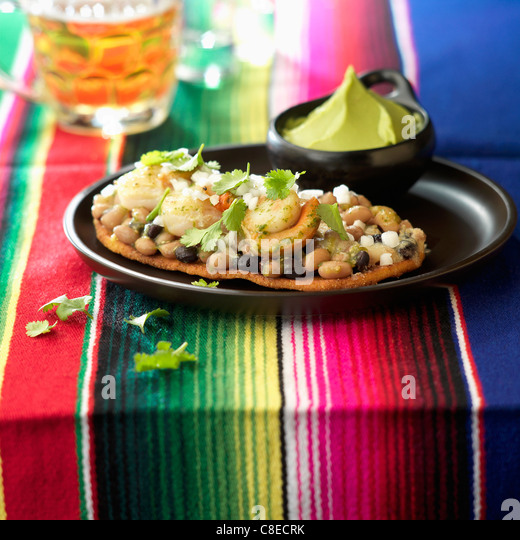 Scallops and two varieties of beans on crisp bread - Stock Image