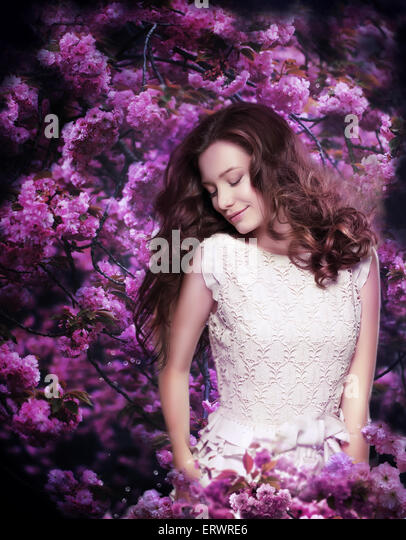 Pure Beauty. Dreamy Young Woman among Flowering Trees - Stock Image