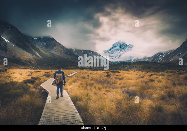 Man Walking On Path To Mountains - Stock Image
