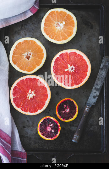 Pink grapefruit and blood oranges on a baking tray. - Stock Image
