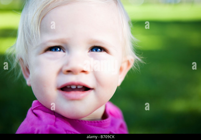 Portrait of a one year old baby girl in the park. - Stock Image