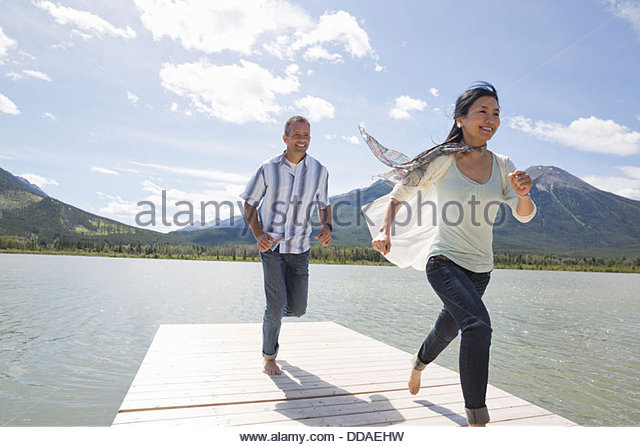 Mature couple running on dock - Stock Image