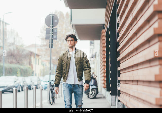 Handsome young man walking outdoor in the city looking away, serious - strolling, everyday life, city living concept - Stock-Bilder
