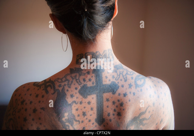 Bare back of woman with tattoos on her neck and back. - Stock-Bilder