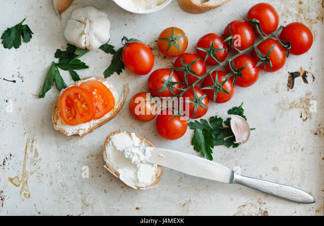 Tomatoes on vine near cream cheese and bread - Stock-Bilder