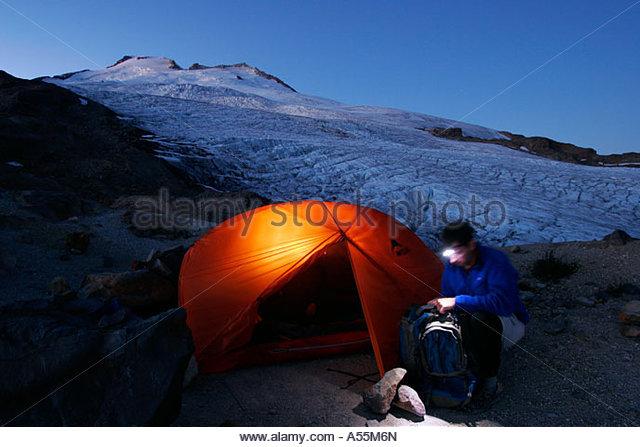 Young man gets ready for tomorrow s climb MSR Hubba Hubba Easton Glacier railroad grade Mt Baker Wilderness Washington - Stock Image