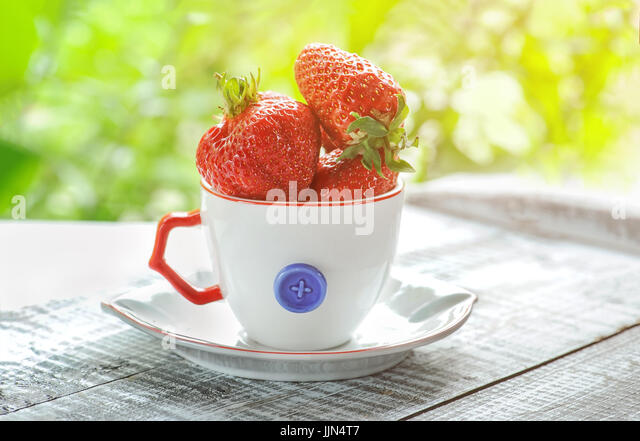 Ripe, red, large strawberries in white Cup decorative with red pen on a green blurred background. - Stock Image
