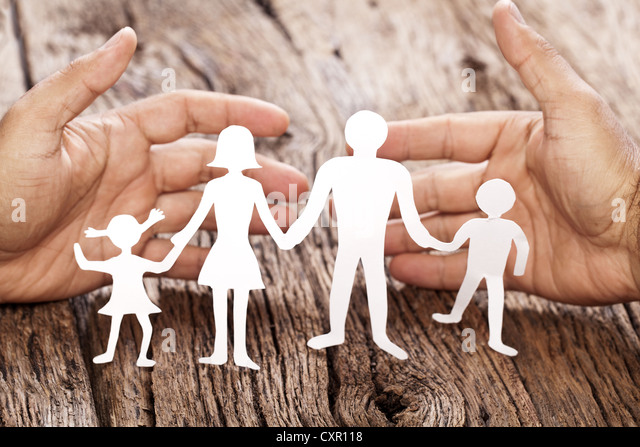 Cardboard figures of the family on a wooden table. The symbol of unity and happiness. Hands gently hug the family. - Stock Image