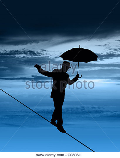 Silhouette of businessman on tightrope - Stock Image