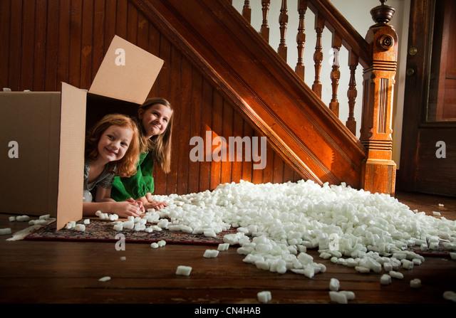 Portrait of girls hiding in cardboard box - Stock Image