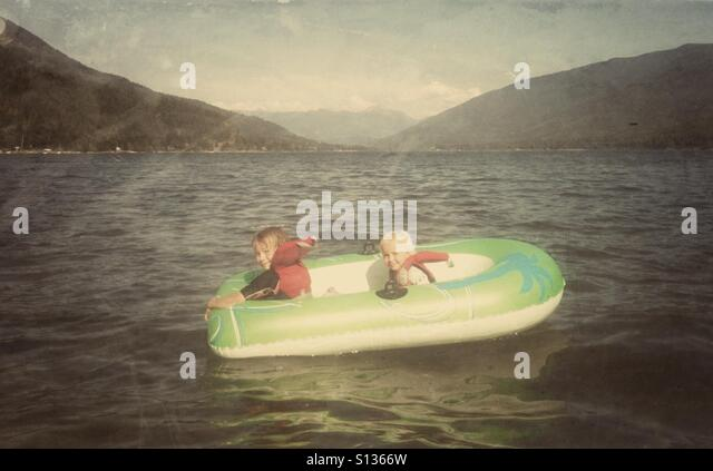 Two children enjoy a sunny day in an inflatable boat on a mountain lake. - Stock Image