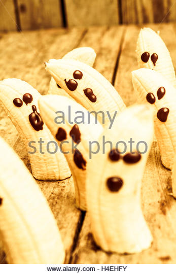 Funny halloween fruit photo on banana ghosts on party decoration table. Creepy event food - Stock Image