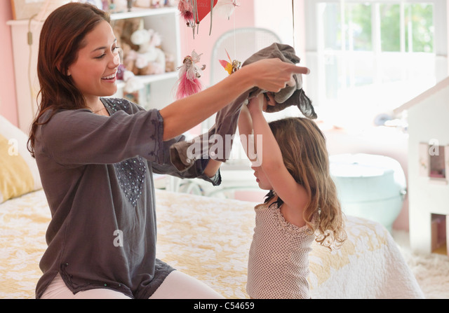 Happy woman dressing her daughter at home - Stock Image