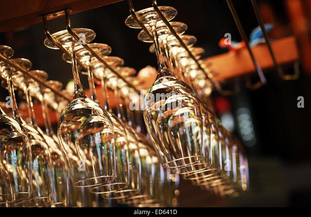 Many empty glasses for a wine hanging in the bar. Close up photo with selective focus - Stock Image
