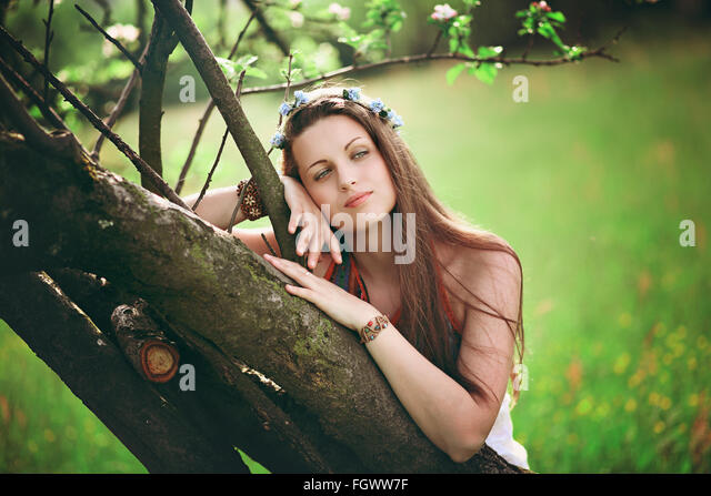 Bohemian woman leaning on spring tree. Hippie and romantic - Stock-Bilder