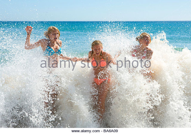 Teenage girls getting splashed by ocean wave - Stock-Bilder