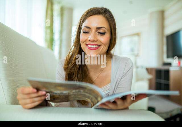 Beautiful woman on a sofa reading a paper in a well lit stylish  living room - Stock Image