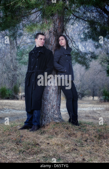 a couple in a conflict-filled atmosphere under a tree - Stock Image