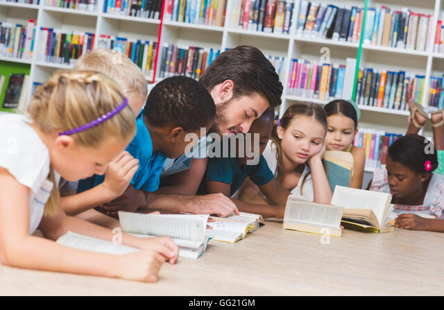 Teacher and kids lying on floor reading book in library - Stock Image