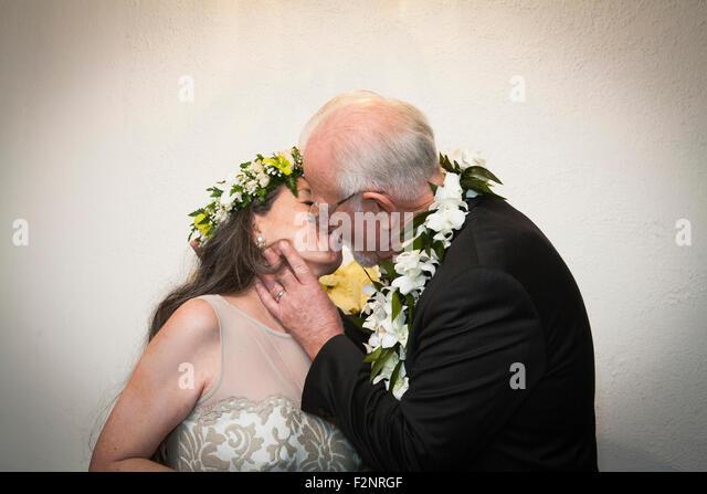 Older bride and groom kissing at wedding - Stock-Bilder