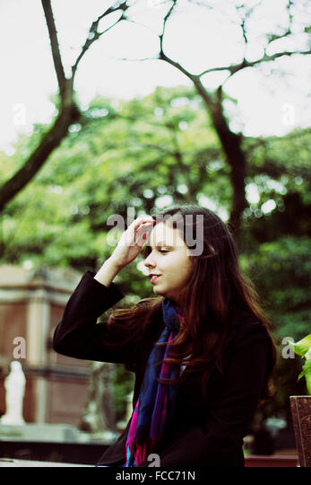 Side View Of A Teenage Girl Against Trees - Stock Image