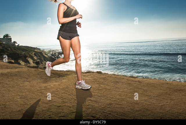 Mid adult woman jogging along cliff - Stock-Bilder