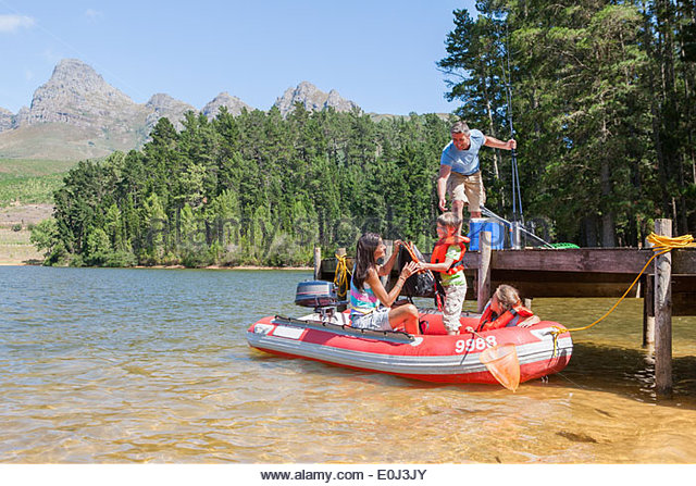 Family Getting Into Inflatable Boat For Fishing Trip - Stock Image