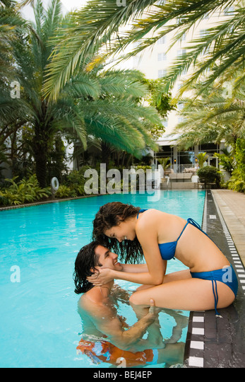Young couple romancing at poolside - Stock-Bilder