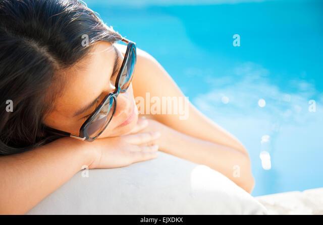 Woman Lying on Swimming Pool Edge - Stock Image