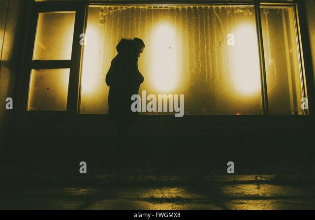 Silhouette of two people dancing against window - Stock Image