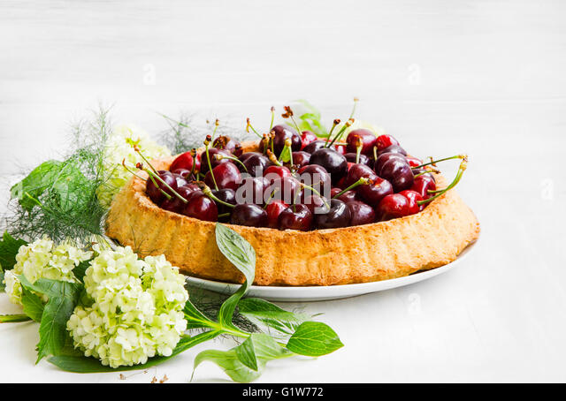 Sweet cherries tart, tasty pie with fresh fruits and white flowers ornament - Stock Image