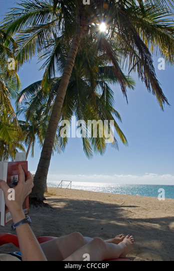Allison Webb reading a book and relaxing at the beach Playa Ancon near Trinidad Cuba - Stock Image