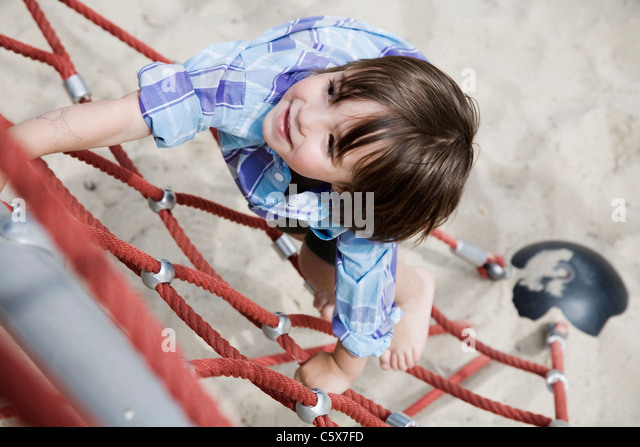 Germany, Berlin, Boy (3-4) at playground climbing on jungle gym, elevated view - Stock-Bilder
