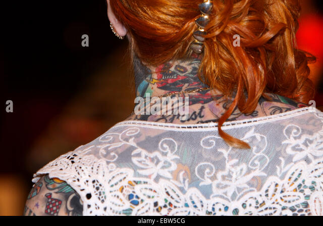 neck of a tattooed red-haired woman - Stock-Bilder